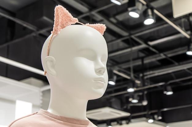 ピンクの耳のヘッドバンドを身に着けている白いプラスチックの赤ちゃんマネキンの頭のクローズアップ。子供服店、カーニバルコスチューム、コスプレ。子供のファッション業界。