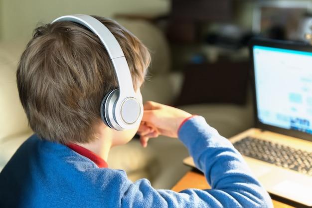 Закройте вверх головы белокурого мальчика ребенка в наушниках сидя на столе с тетрадью. обучение на дому и обучение из дома онлайн