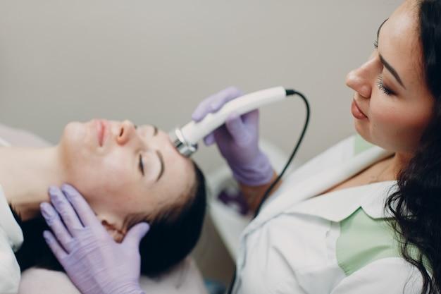ビューティースパサロンでエレクトロポレーションフォノフォレシスフェイシャルセラピーを受けている頭の女性のクローズアップ。