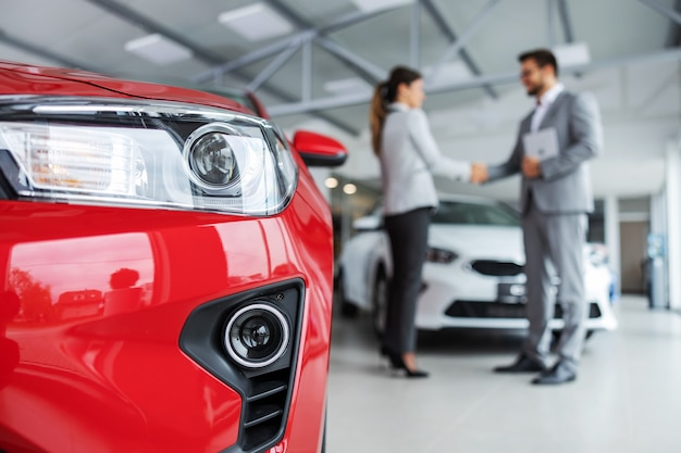 자동차의 헤드 라이트 닫습니다. 흐린 배경에는 자동차 판매자와 악수하는 고객이 있습니다.