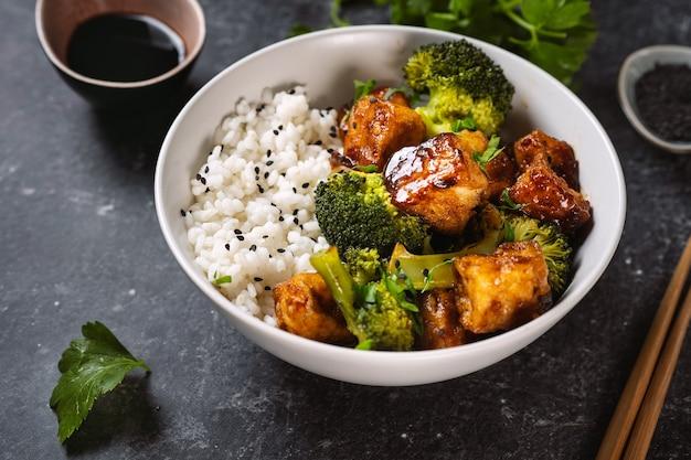 브로콜리와 쌀 검은 배경에 건강한 두부 그릇 닫습니다