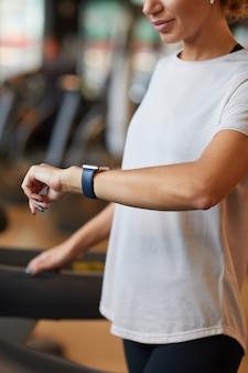 彼女の腕の時計を見て、ジムのトレッドミルでトレーニングしながら彼女の脈拍をチェックしている健康な女性のクローズアップ