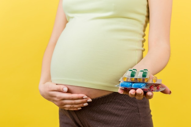 Закройте вверх кучи волдырей пилюлек в руке беременной женщины на красочной предпосылке с космосом экземпляра. здравоохранение и лечение во время беременности