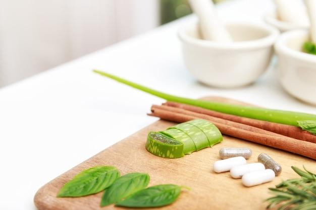 白いテーブルの上の自然な代替療法で使用される新鮮なハーブとドライフラワー、アロマテラピーエッセンシャルオイルと乳棒を使った乳鉢を使った漢方薬の準備のクローズアップ。
