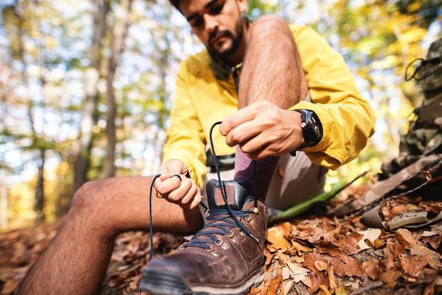 秋の森の中で地面に座っている間ハイカー抱き合わせ靴のクローズアップ。