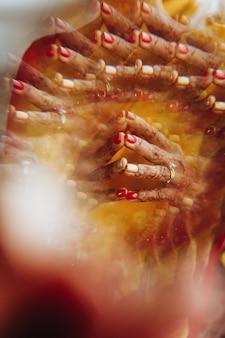 ヘナタトゥーで覆われているヒンズー教の花嫁の手のクローズアップ