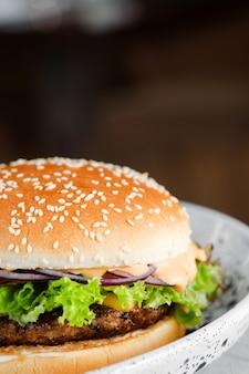 Крупный план домашнего вкусного гамбургера в керамической тарелке