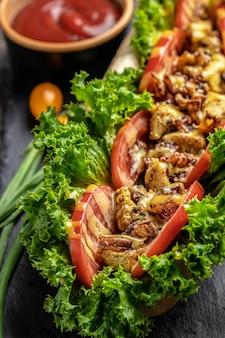 Крупным планом домашний вкусный хот-дог с луком. жареное мясо, помидоры, листья салата и сырный соус, вид сверху