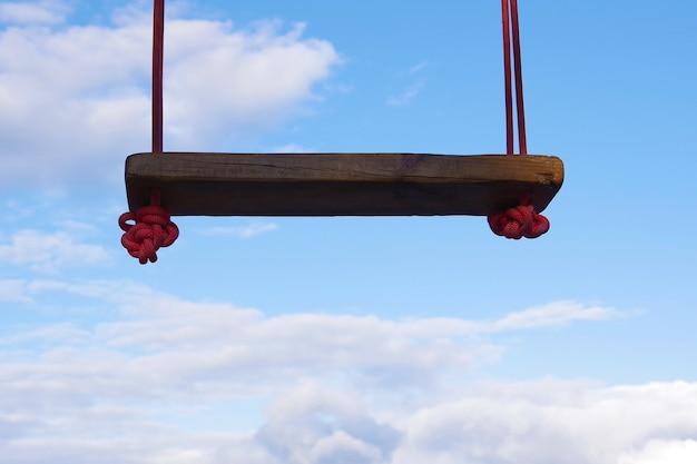 Крупный план самодельных деревянных качелей на фоне облаков. концепция полета, мечтания, счастья.