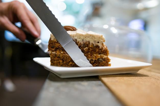 커피숍에서 접시에 제공되는 집에서 만든 건강한 당근 케이크 부분을 클로즈업합니다.