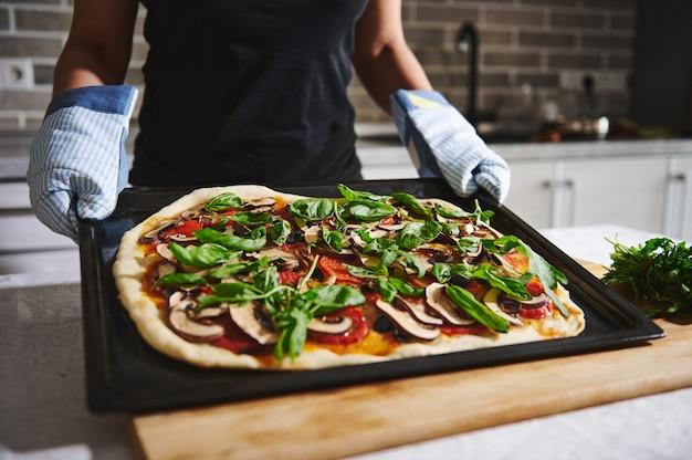 キッチンミトンの手でオーブンから自家製ビーガンピザのクローズアップ。ベジタリアンピザを持っている女性