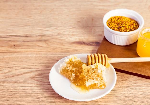 Крупный план соты и пчелиная пыльца на деревянный стол