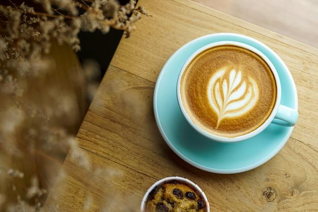 カップマグカップにラテアートミルクフォームとカフェのコーヒーショップの木製デスクオフィスデスクに自家製バナナカップケーキを入れたホットコーヒーラテのクローズアップ、ビジネスワークコンセプト中