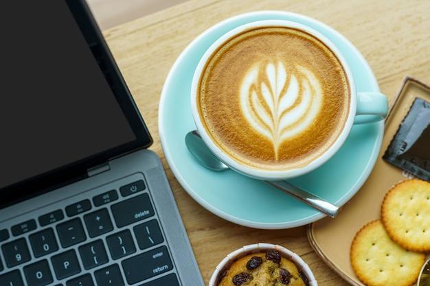 Крупный план горячего кофе латте с молочной пеной латте арт в кружке чашки и домашнего бананового торта с портативным компьютером на деревянном столе офисного стола в кафе в кафе, во время концепции бизнес-работы