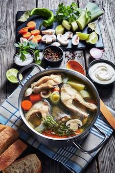Крупный план острого острого рыбного супа из форели с овощами и грибами в кастрюле на деревянном деревенском столе с ингредиентами, вертикальный вид сверху