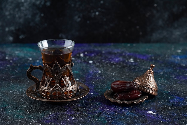 青い表面の熱いお茶と乾いた日付のクローズアップ