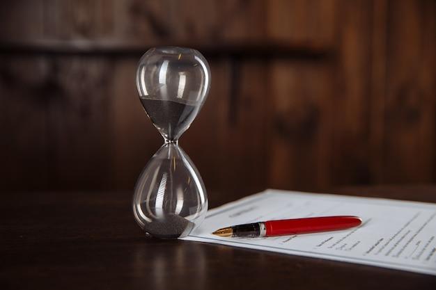 Крупный план измерения времени песочными часами, официальное подписание контракта.