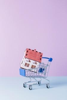 Крупный план модели дома в корзине покупок