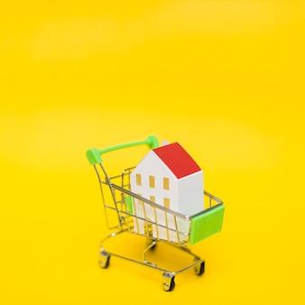 노란색 배경 미니어처 쇼핑 카트에 집 모델의 클로즈업