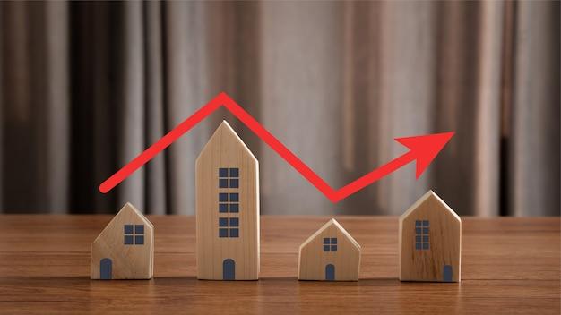 Закройте модель дома с красной стрелкой, указывающей вверх, так же, как ступенчатая лестница поднимается. концепция недвижимости.
