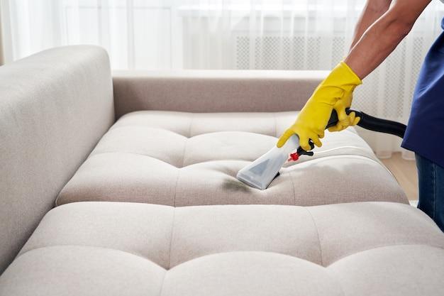 Крупным планом экономка держит современный стиральный пылесос и чистит грязный диван профессиональным моющим средством. концепция профессиональной весенней уборки в домашних условиях