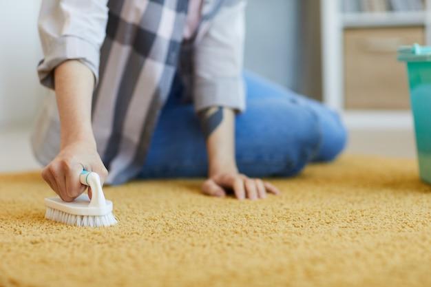 바닥에 앉아 집에서 브러시로 카펫을 씻는 가정부의 근접