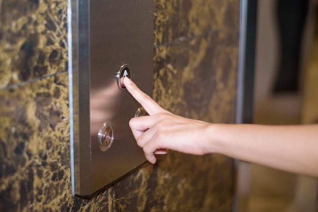 닫기 인간 손가락의 엘리베이터 버튼을 밀고있다