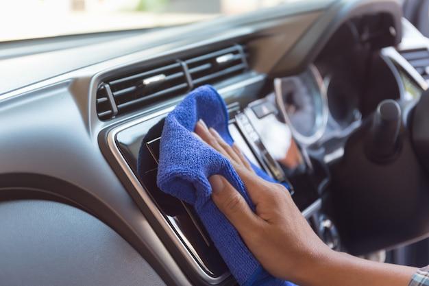 人間の手のクローズアップは車で掃除しています。