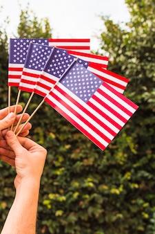 Крупный план человеческой руки, держащей американские флаги сша