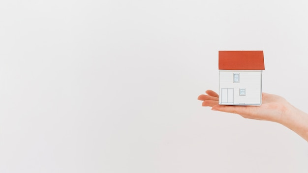 흰색 배경에서 인간의 손 잡고 미니 하우스 모델의 클로즈업