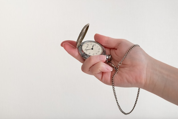 가벼운 표면에 오래 된 회중 시계를 들고 인간 손의 근접