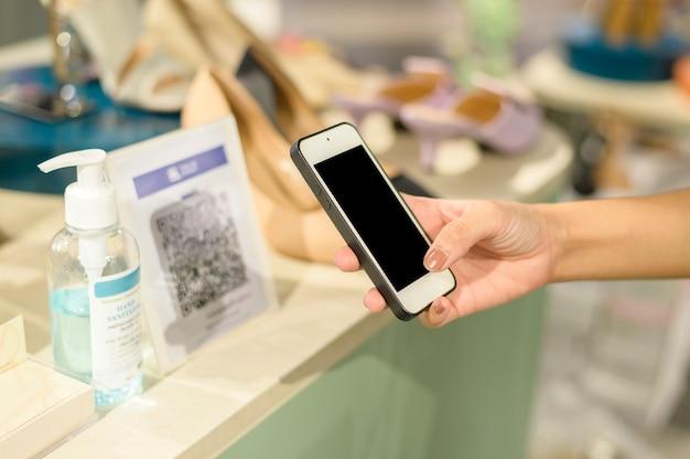 人間の手のクローズアップはショッピングモールで支払うスマートフォンを保持しています。