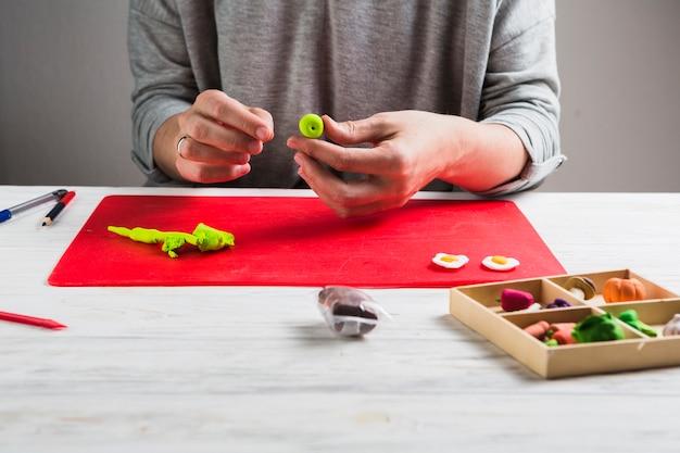 緑の粘土から形を作る人間の手のクローズアップ
