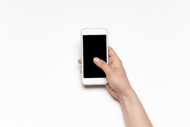 Закройте человеческую руку с помощью смартфона с пустым черным экраном