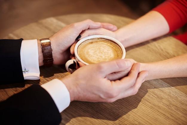 커피 한 잔을 들고 인간의 손을 닫습니다