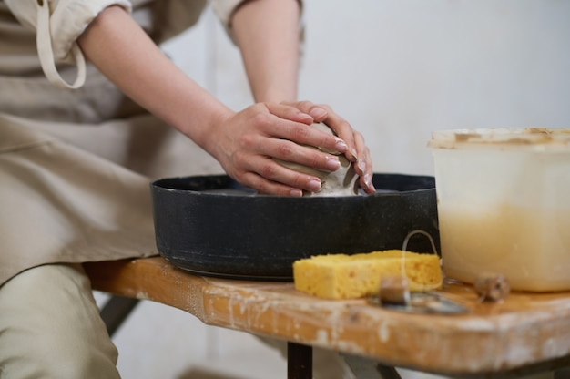 Крупным планом человеческие руки лепят глину на гончарном круге