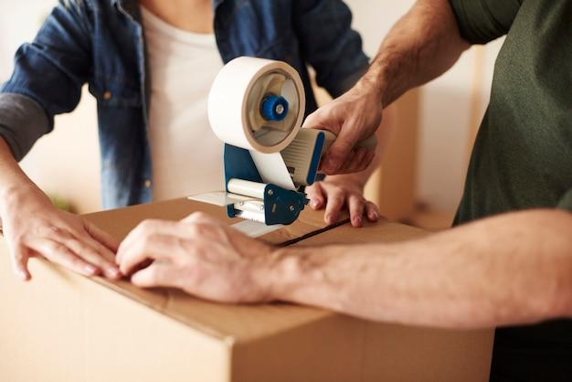 Закройте человеческие руки, вставляя картонные коробки