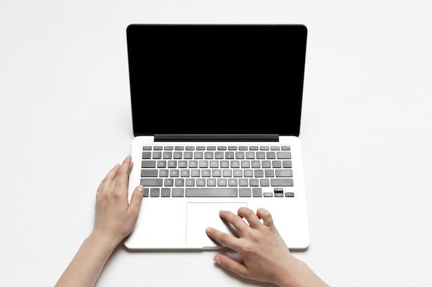 Закройте человеческих рук, используя ноутбук, изолированные на белом фоне. вид сверху. copyspace, пустой экран. серфинг, интернет-покупки, скроллинг, ставки, работа. концепция образования и бизнеса.