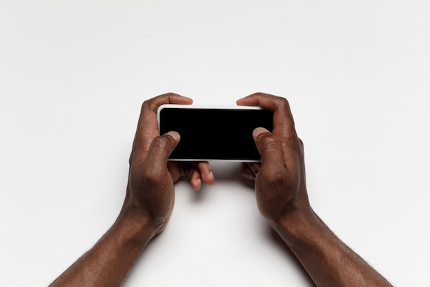 Крупным планом человеческих рук с помощью смартфона, изолированные на белом фоне. вид сверху. copyspace, пустой экран. серфинг, интернет-покупки, скроллинг, ставки, работа. концепция образования и бизнеса.