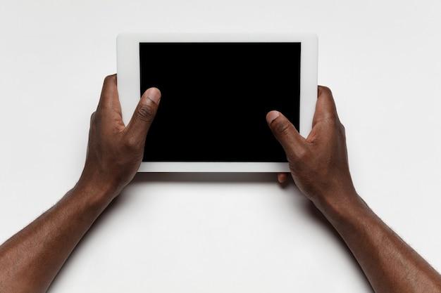 Крупным планом человеческих рук с помощью планшета с пустым черным экраном