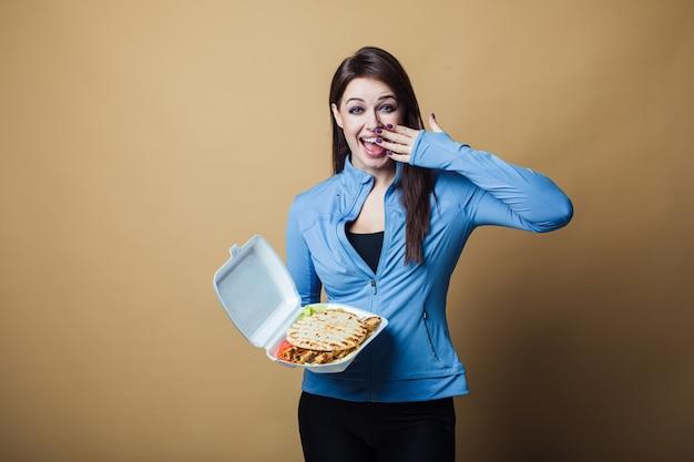 大きなサンドイッチを保持し、食べて、口を開けて空腹の女性のクローズアップ。ファーストフードのコンセプト
