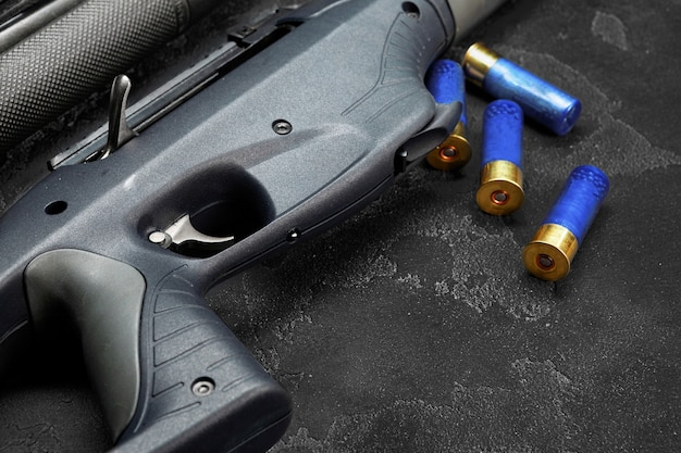 Крупным планом охотничье ружье и патроны на темно-сером фоне