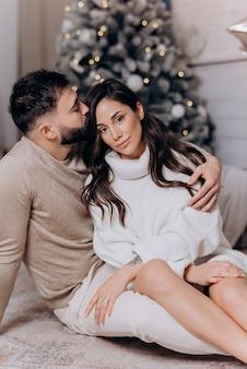 남편이 껴안고 바닥에 앉아 있는 흰색 스웨터를 입은 아름다운 아내에게 키스를 하세요