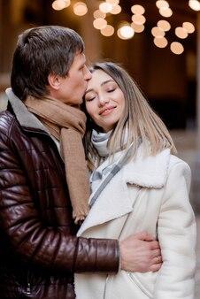 남편이 도시를 산책하는 동안 아내에게 키스하는 것을 클로즈업