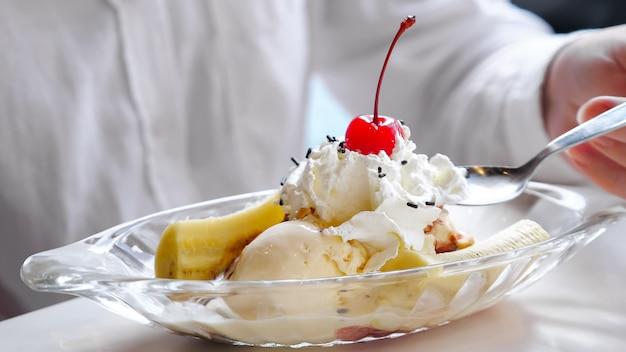 Крупный план мороженого со взбитыми сливками, бананом и вишней.