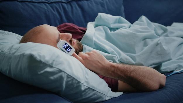 指にオキシメータとソファで寝ている病気の人のクローズアップ