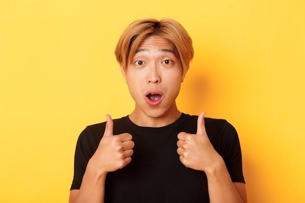 親指を現して驚いて、黄色の壁の上に立って、印象的で興奮しているハンサムなアジア人のクローズアップ