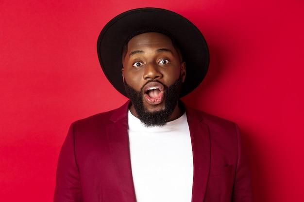 カメラを見つめ、あごを落とし、赤い背景の上に立って驚いて見えるひげを持つ印象的な黒人男性のクローズアップ