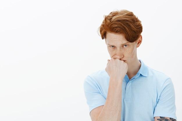 Крупный план нерешительного красивого рыжего мужчины, выглядящего обеспокоенным, думая