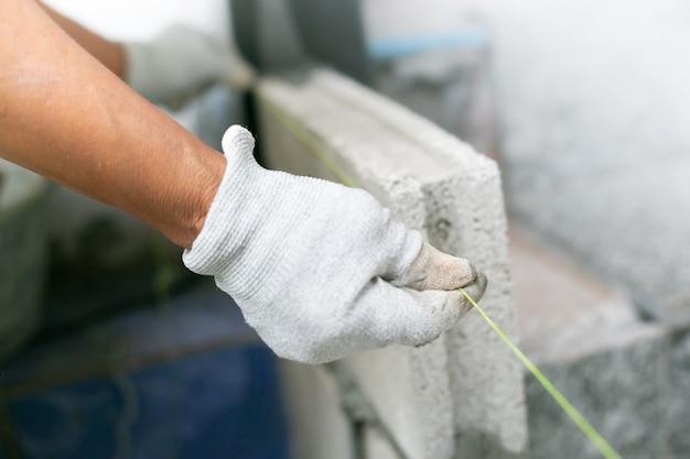 工事現場、建物の壁にレンガをインストールしている工業用レンガのクローズアップ。